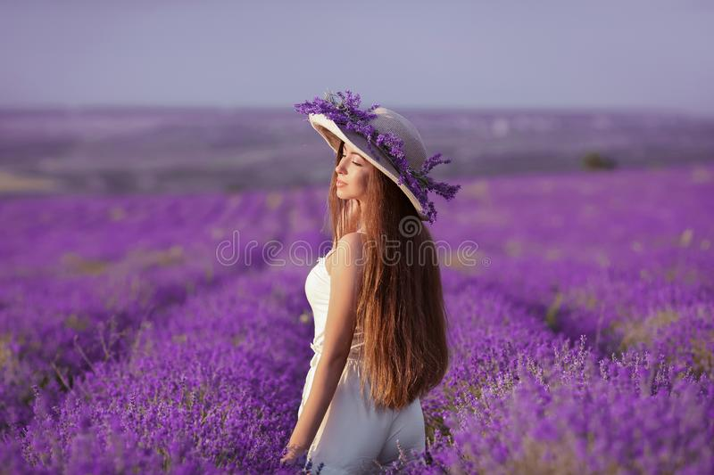 Beautiful healthy long hair. Back view of Young teen girl in hat. Over lavender field. Happy carefree woman with shiny hairstyle enjoying sunset. Outdoors royalty free stock image