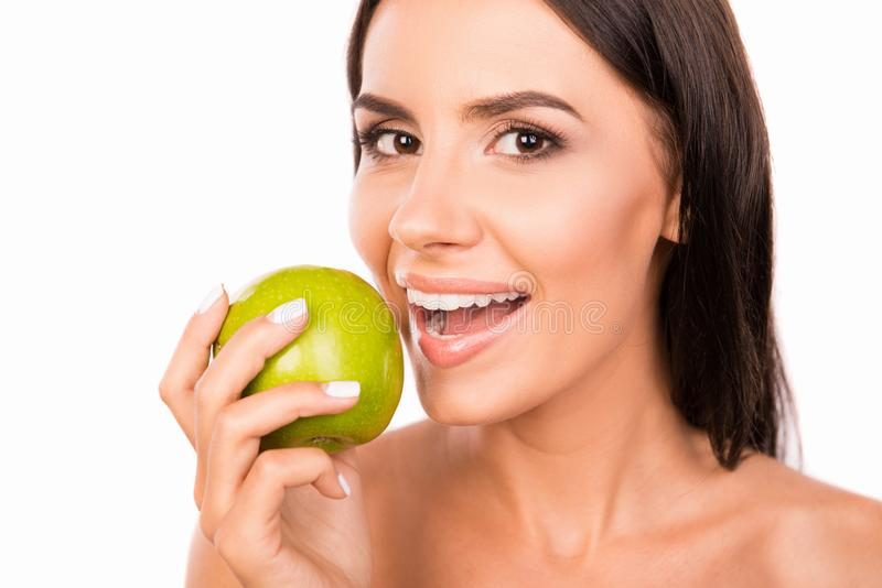 Beautiful healthy toothy girl biting green apple royalty free stock images
