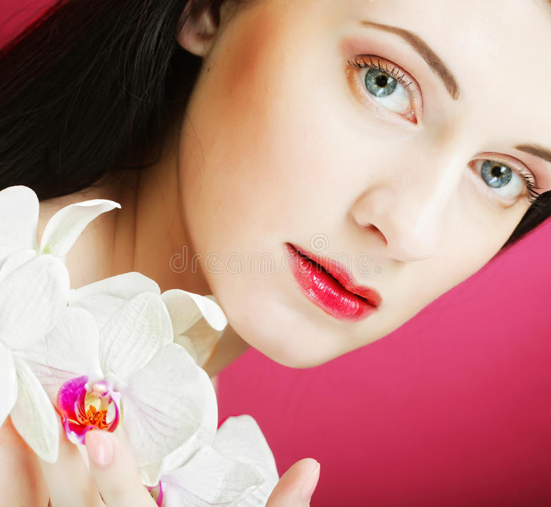 Beautiful Healthy Woman With Orchid Flower. Stock Photo