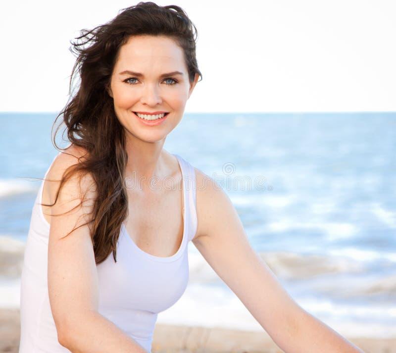 Beautiful healthy woman sitting on beach stock photography