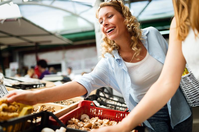 Beautiful happy women shopping vegetables and fruits stock photography