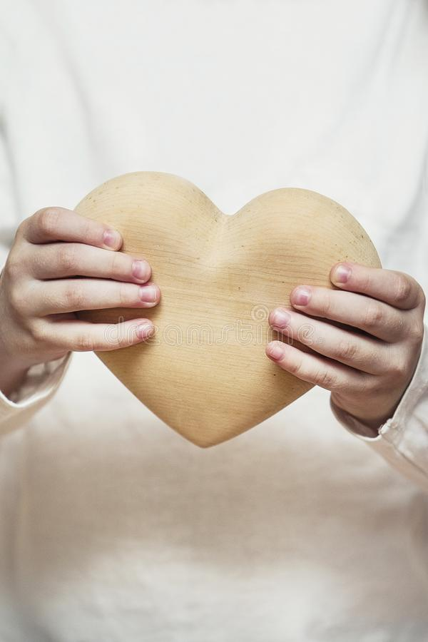 Beautiful heart made of wood in children hands royalty free stock images