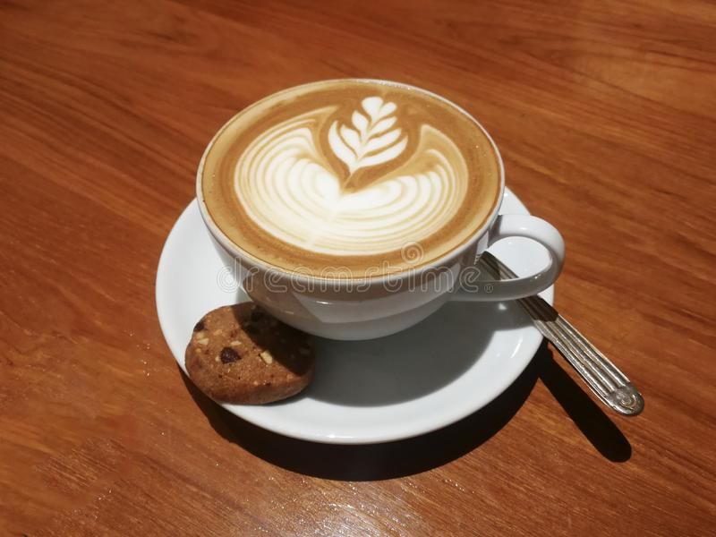 Beautiful heart shapes Latte art on wooden table. Beautiful heart shapes Latte art with biscuit and spoon on wooden table stock photography