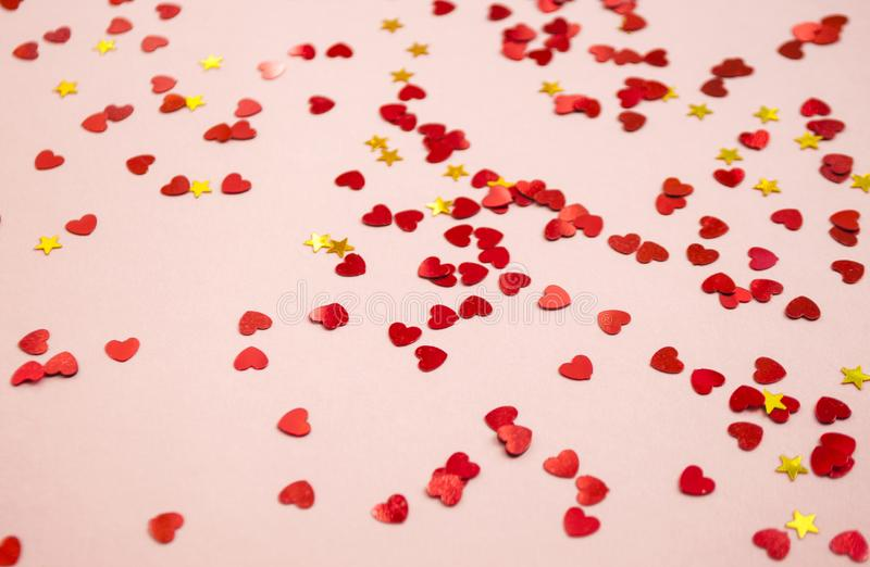 Heart shaped red color confetti on pink background. royalty free stock images