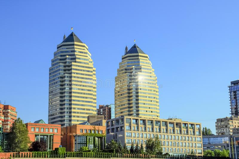 Beautiful high brick skyscrapers, towers and buildings in white and orange with a sun flare. View of the Dnipro city stock image