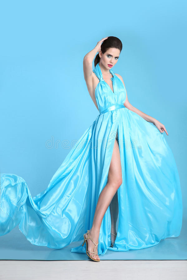 Beautiful High fashion woman in blue dress posing in studio. Glamour model in blowing chiffon dress. Stunning Woman in long royalty free stock photography