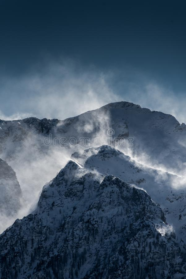 Beautiful high snowy and foggy mountains with snow being blown by wind royalty free stock image