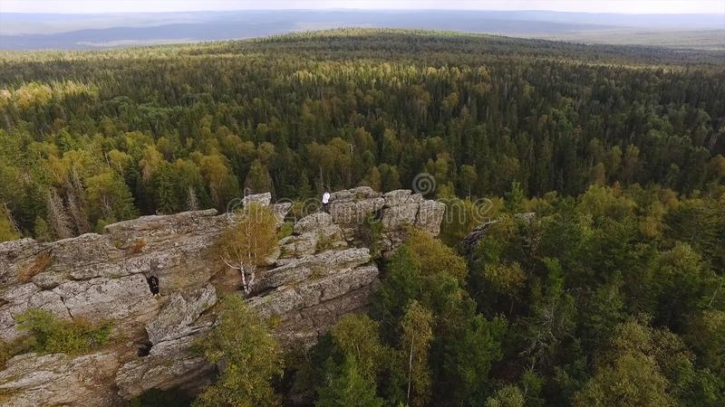 Beautiful high stone rock in green forest under blue sky. Footage. Top view of man standing on rock in thick green. Forest reaching horizon in autumn stock images