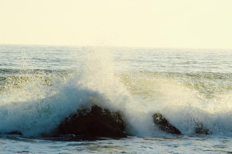 The beautiful high waves in the ocean in Marina di Massa in Italy with a view to the beach with nice colours of the sunset. stock image