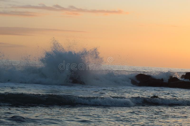 The beautiful high waves in the ocean in Marina di Massa in Italy with a view to the beach with nice colours of the sunset. stock photography