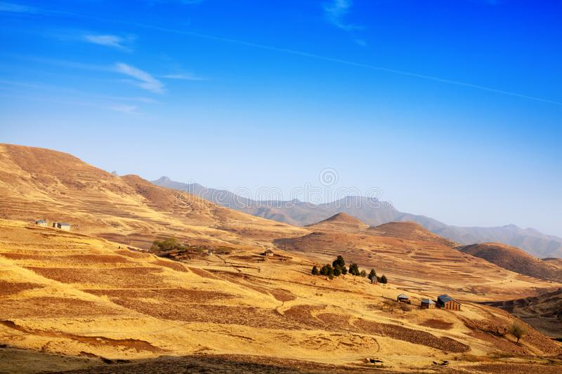 Beautiful highland valley landscape Drakensberg mountains yellow slopes and peaks scenery panoramic view, Lesotho called Kingdom. In the clouds, bright blue royalty free stock photo