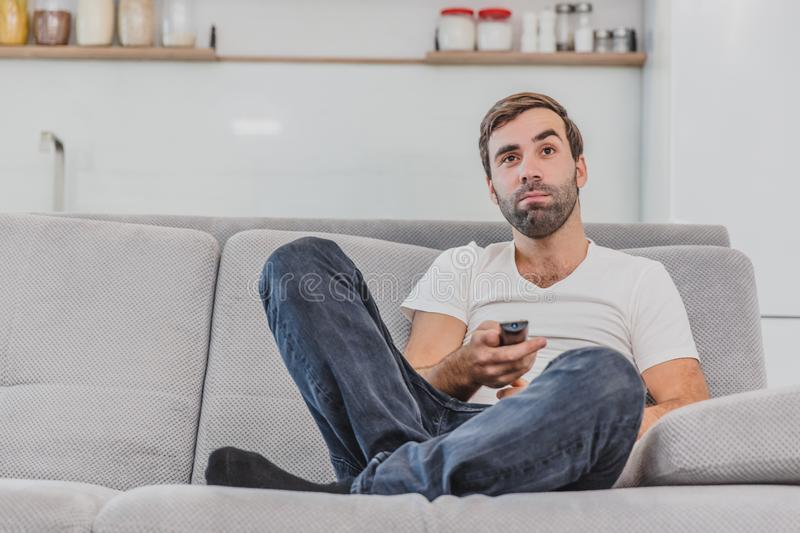 Beautiful hilarious young man holding a remote control. During this, the TV is watching while sitting on the couch at. Home. Dressed in a white T-shirt and stock image