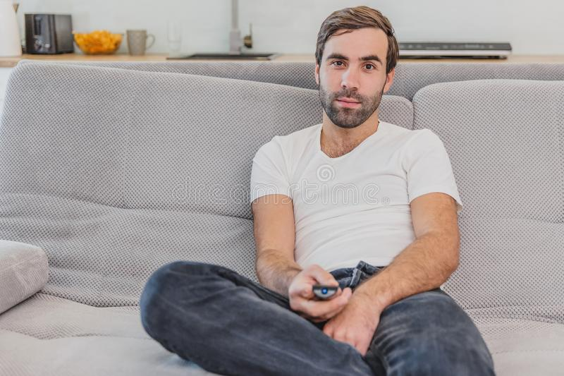 Beautiful hilarious young man holding a remote control. During this, the TV is watching while sitting on the couch at. Home. Dressed in a white T-shirt and royalty free stock image