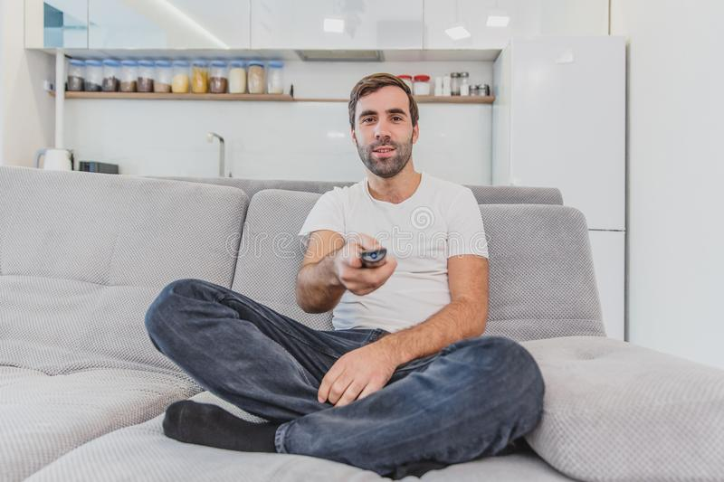 Beautiful hilarious young man holding a remote control. During this, the TV is watching while sitting on the couch at. Home. Dressed in a white T-shirt and royalty free stock images