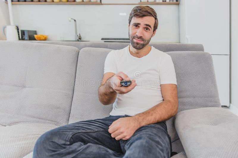 Beautiful hilarious young man holding a remote control. During this, the TV is watching while sitting on the couch at. Home. Dressed in a white T-shirt and stock images