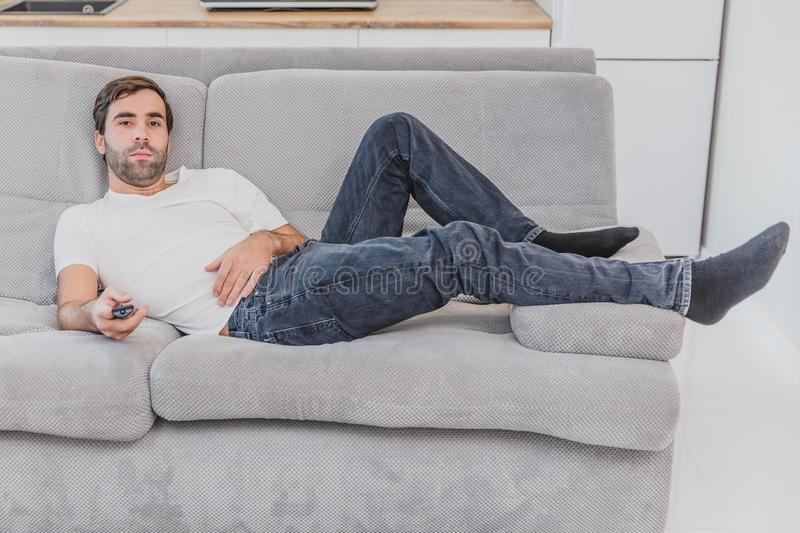 Beautiful hilarious young man holding a remote control. During this, the TV is watching while sitting on the couch at. Home. Dressed in a white T-shirt and royalty free stock photos