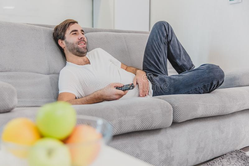 Beautiful hilarious young man holding a remote control. During this, the TV is watching while sitting on the couch at. Home. Dressed in a white T-shirt and stock photos
