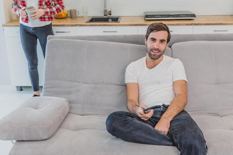 Beautiful hilarious young man holding a remote control. During this, the TV is watching while sitting on the couch at. Beautiful hilarious young men holding a stock photo