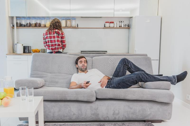 Beautiful hilarious young man holding a remote control. During this, the TV is watching while sitting on the couch at. Beautiful hilarious young men holding a stock image