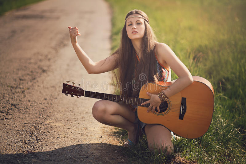 Beautiful hippie hitch-hiker with guitar royalty free stock images