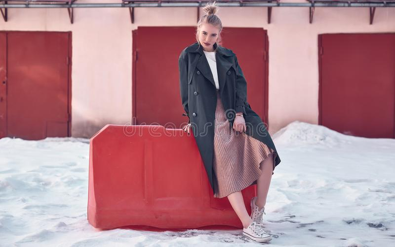 Beautiful hipster blonde woman wearing fashion long coat and dress on the street royalty free stock photography