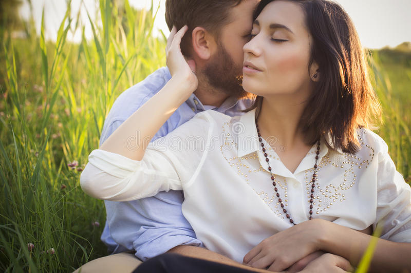 Beautiful hipster couple in love on a date outdoors in park having fun. Bearded redhair man. Brunette woman in black skirt and stock photos