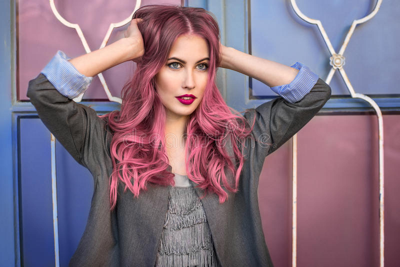 Beautiful hipster fashion model with curly pink hair posing near the colorful wall royalty free stock image