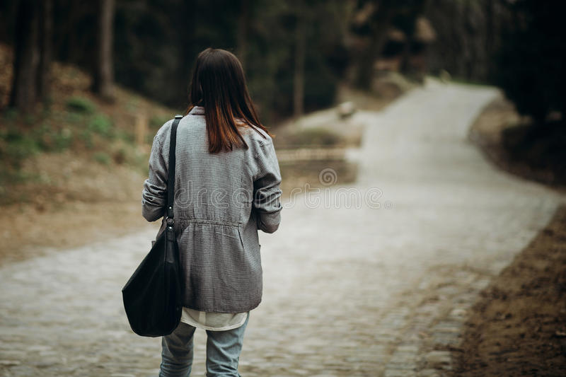 Beautiful hipster girl with black leather purse walking down pavement road in the countryside, young woman tourist in stylish stock photos