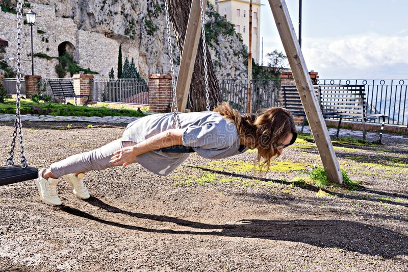 Beautiful hipster girl in casual look and swing. Joyful, beautiful hipster girl in casual look and windy hair, fooling around on swing planking, deadpan style royalty free stock photo