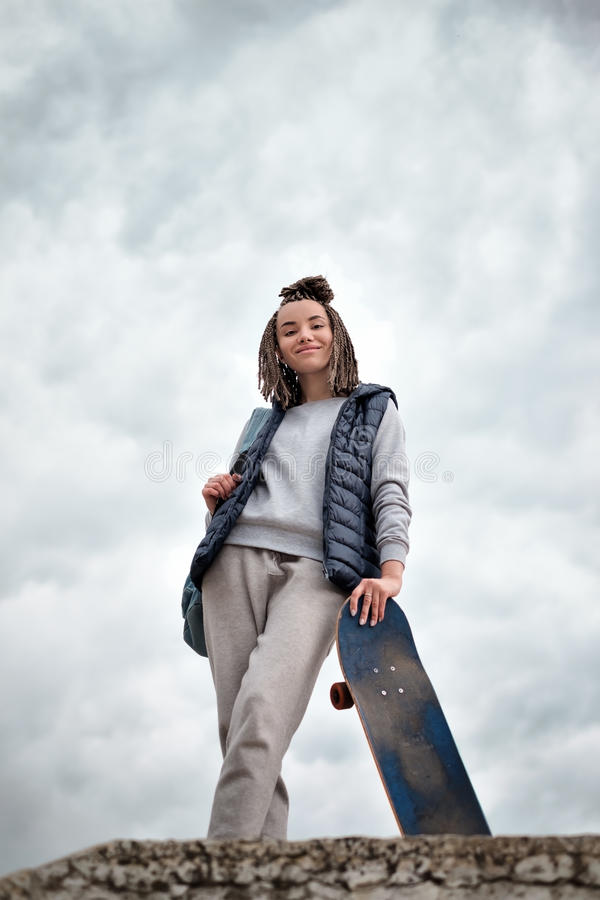 Beautiful hipster girl with skate board standing with smile royalty free stock images