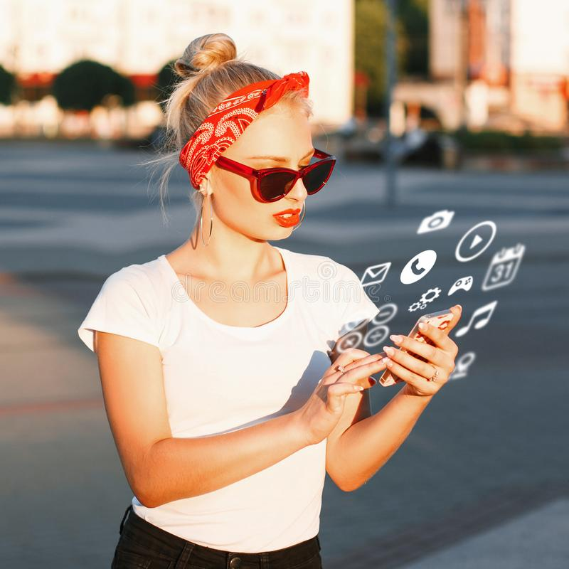 Beautiful hipster girl with sunglasses holding a phone with flying icons. stock image