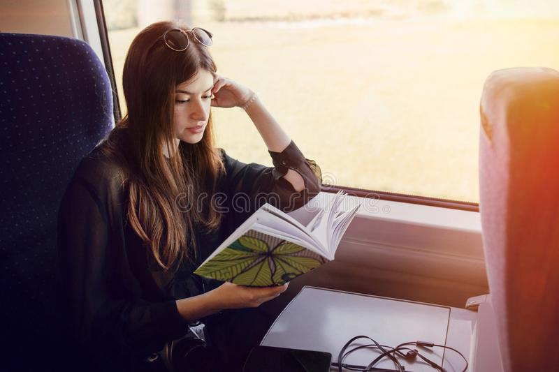 beautiful hipster girl traveling by train and holding book. stylish happy woman reading book at window light in train. travel and stock image