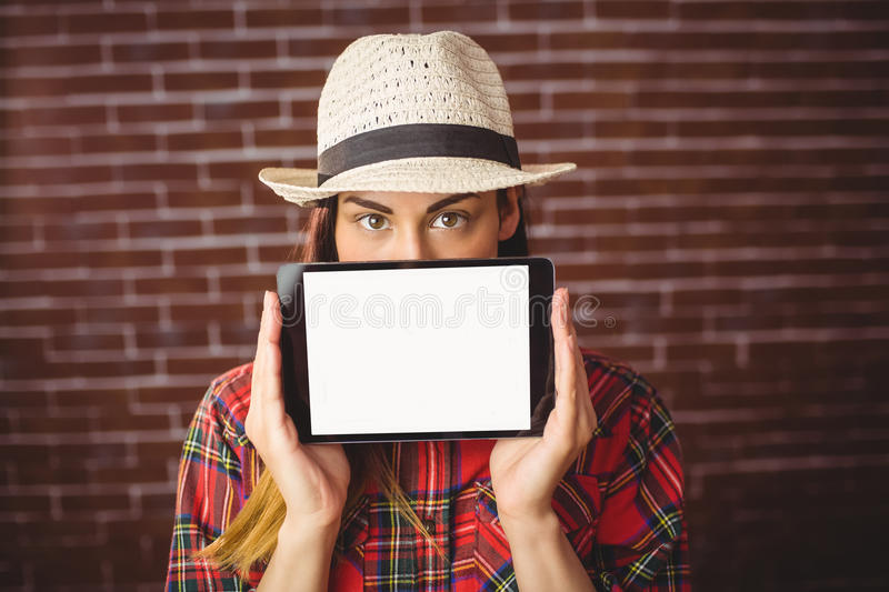 Beautiful hipster showing tablet to camera. On red brick background royalty free stock photo