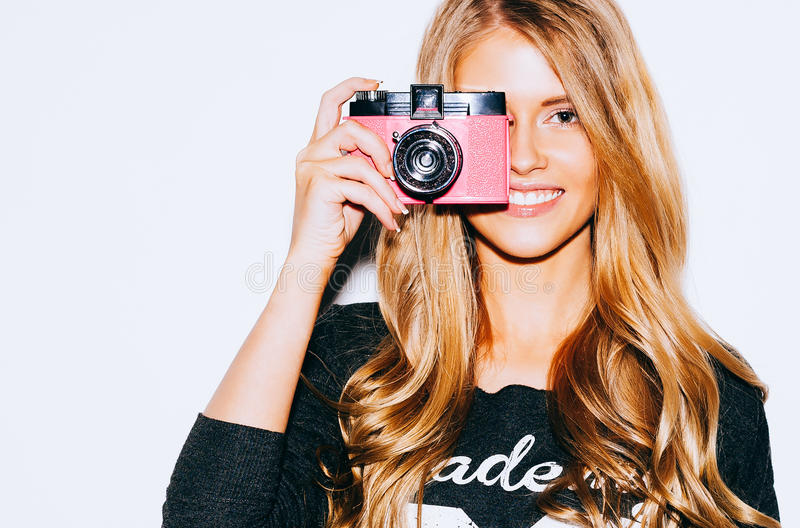 Beautiful Hipster woman taking photos with pink retro film camera on white background. Close up. Indoor. Warm color. royalty free stock photography