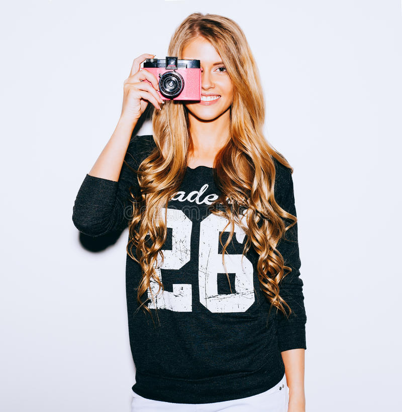 Beautiful Hipster woman taking photos with pink retro film camera on white background. Hair style. Indoor. Warm color. royalty free stock photo