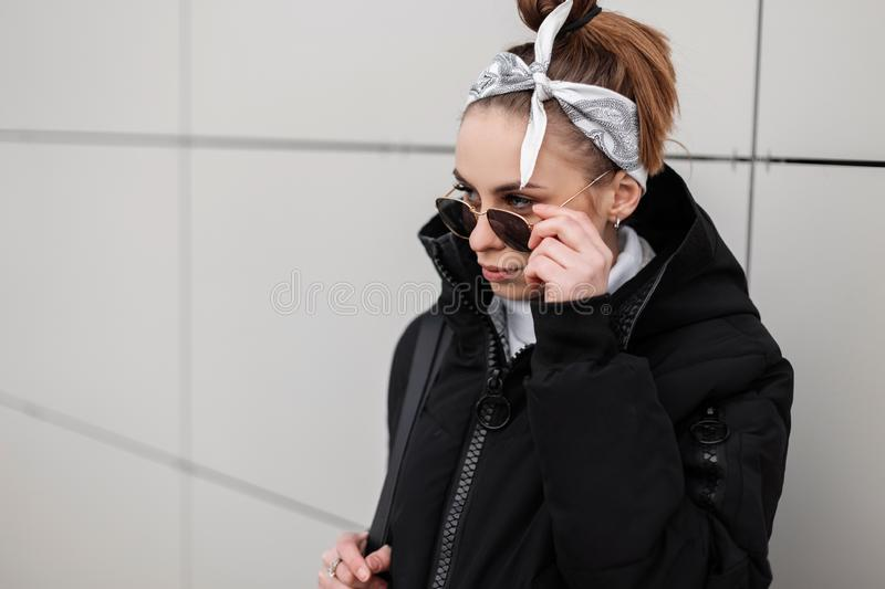 Beautiful hipster young woman with a fashionable hairstyle with a stylish bandana in black sunglasses in a trendy black jacket. Poses near the wall on a winter royalty free stock photography