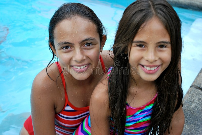 Beautiful Hispanic sisters by the pool stock images