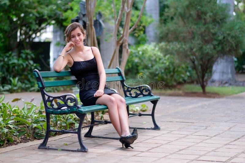 Beautiful hispanic teenage girl sitting on a park. Beautiful hispanic teenage girl sitting on a wooden bench on a park royalty free stock photo