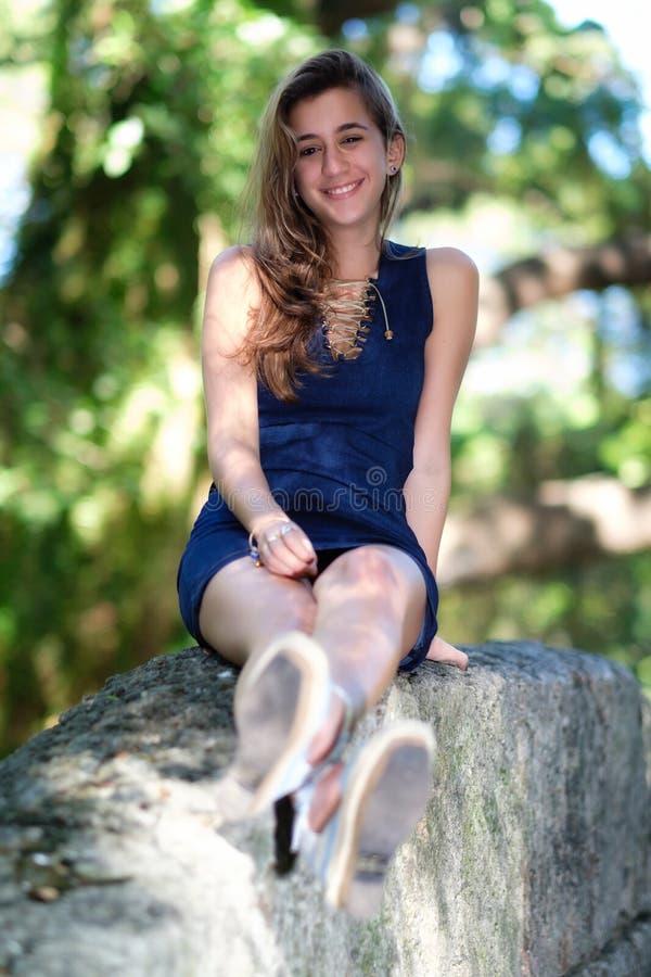 Beautiful hispanic teenage girl smiling. With a diffused vegetation background stock photos