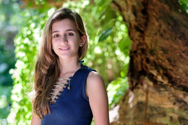 Beautiful hispanic teenage girl. Smiling with a diffused vegetation background stock photos