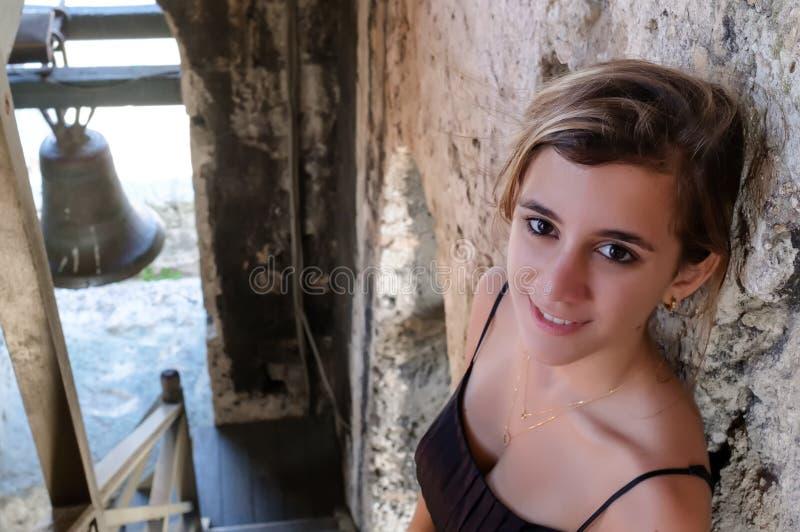 Beautiful hispanic teenage girl standing on an old staircase. On a church belfry stock image