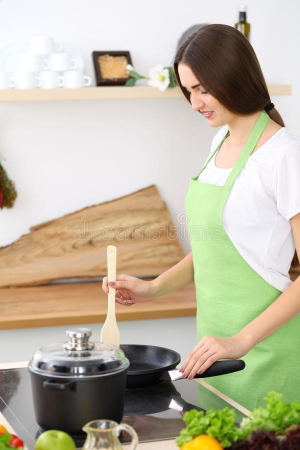 Beautiful Hispanic woman cooking in kitchen. Girl frying in a skillet something. Healthy meal and householding concepts.  stock image