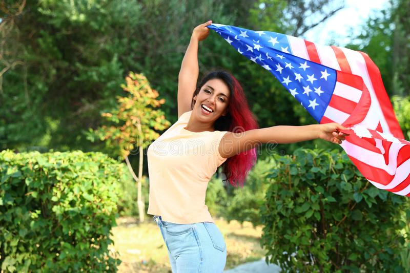 Beautiful Hispanic woman with US flag in. Park royalty free stock photos