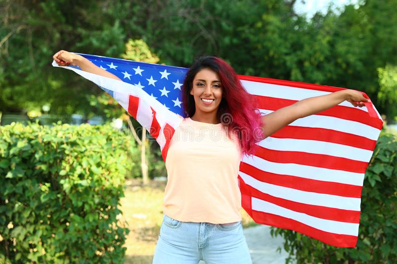 Beautiful Hispanic woman with US flag in. Park stock photos