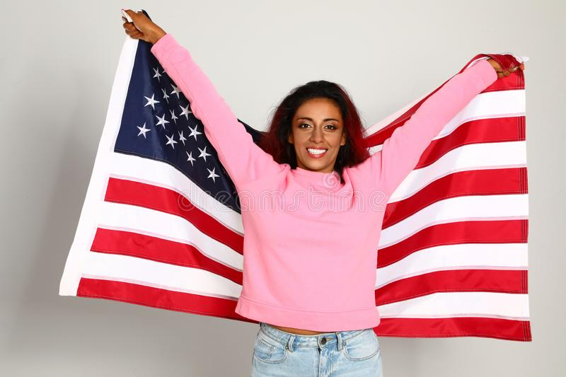 Beautiful Hispanic woman with US flag on  background. Beautiful Hispanic woman with US flag on light background royalty free stock photography