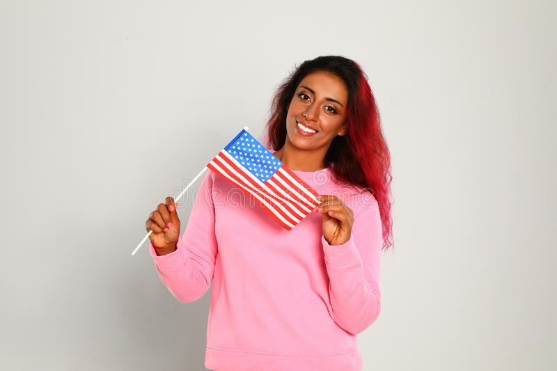 Beautiful Hispanic woman with US flag on light. Background stock photo