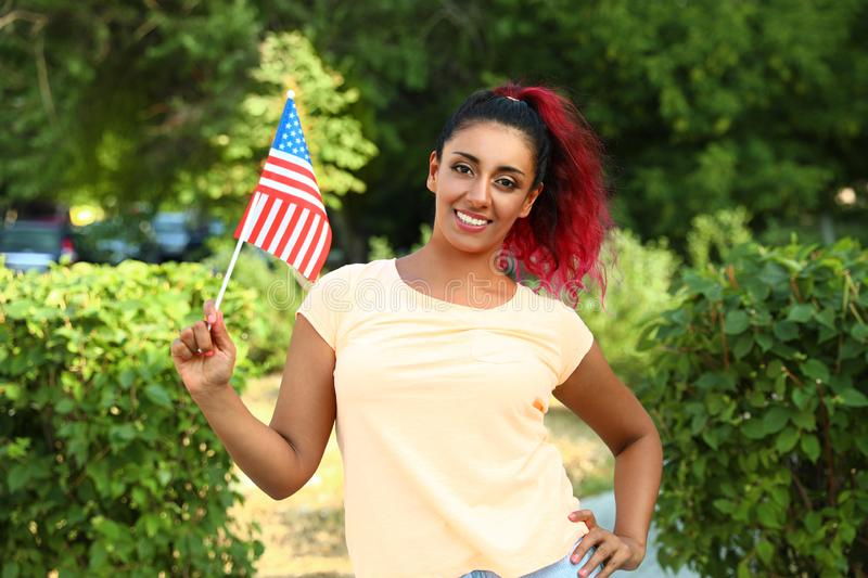 Beautiful Hispanic woman with US flag in. Park royalty free stock photo