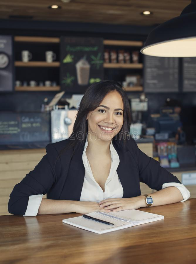 Beautiful hispanic young woman in suit working at the cafe stock photo