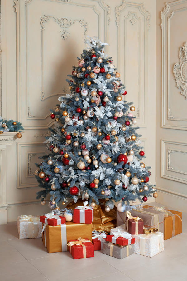 Beautiful holdiay decorated room with Christmas tree and presents under it. New Year decorations royalty free stock image