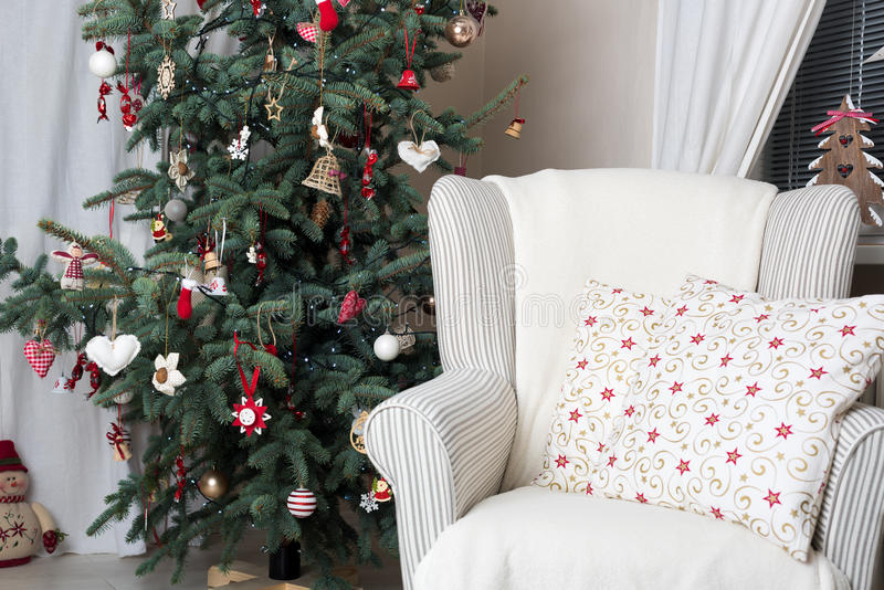 Beautiful holiday decorated room with Christmas tree and white comfortable chair stock image